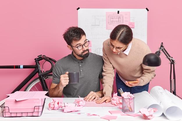 Zwei grafikdesigner arbeiten gemeinsam an bauskizzen und teilen unterschiedliche ideen für die erstellung eines neuen raum-brainstormings gemeinsam posieren auf dem desktop