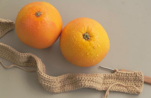 Zwei grapefruits neben strickarbeit, auf hintergrund, verschwommenes licht herum