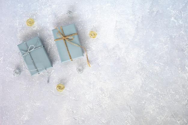 Zwei graue geschenkboxen verzierten silberne und goldene bänder auf grauem hintergrund, urlaubskonzept, weihnachten, geburtstag, draufsicht, kopierraum