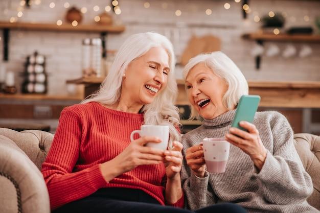 Zwei grauhaarige angenehme süße damen, die auf dem sofa sitzen und lachen