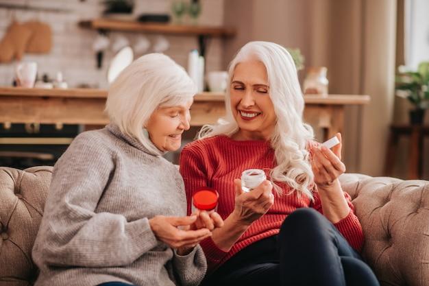 Zwei grauhaarige angenehme süße damen diskutieren über neue kosmetika