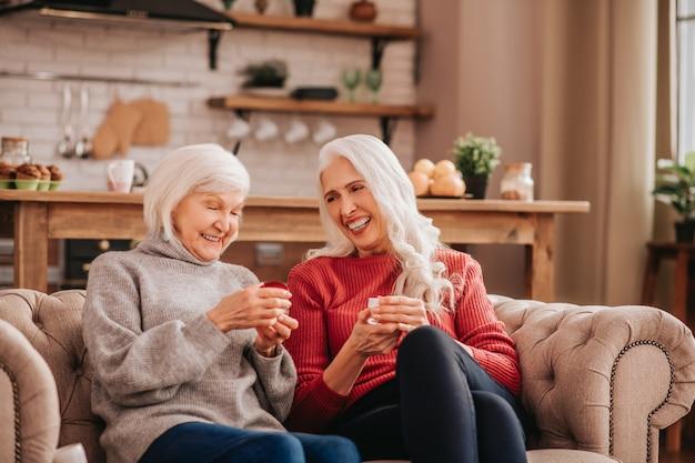 Zwei grauhaarige, angenehme, süße damen sprechen über hautpflege