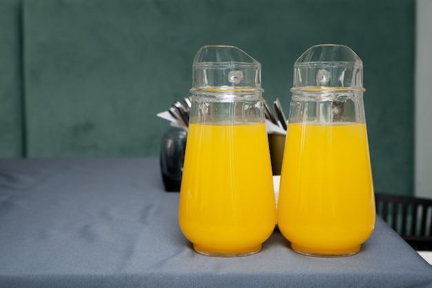 Zwei große durchsichtige krüge mit früchten trinken. orangensaft auf grauem tisch.