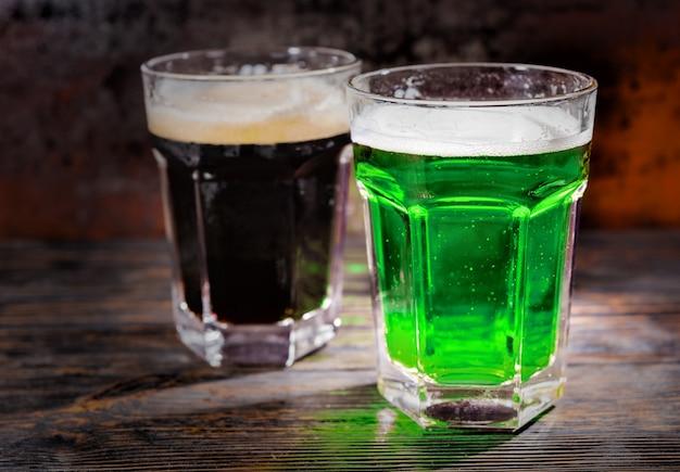 Zwei große gläser mit frisch eingegossenem dunklem und grünem bier auf holzschreibtisch. lebensmittel- und getränkekonzept