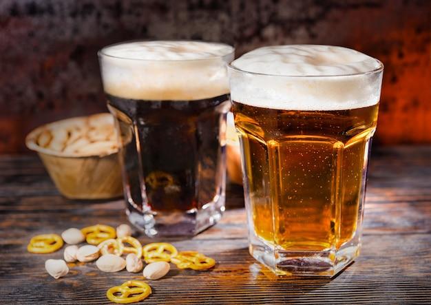Zwei große gläser mit frisch eingegossenem dunklem und hellem bier in der nähe von verstreuten kleinen brezeln und pistazien auf einem dunklen holzschreibtisch. lebensmittel- und getränkekonzept