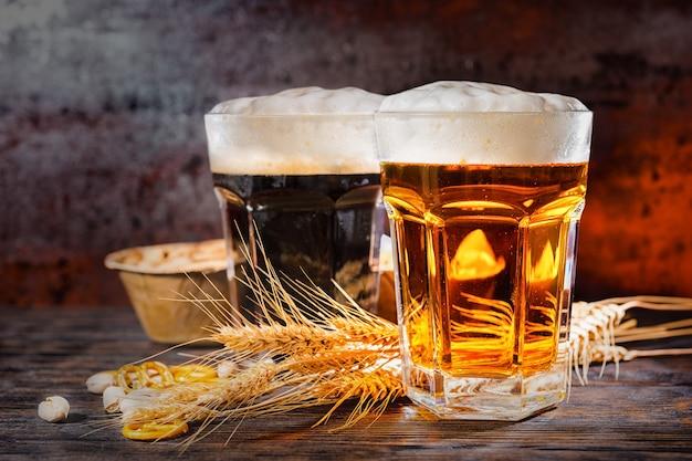Zwei große gläser mit frisch eingegossenem dunklem und hellem bier in der nähe von weizen, verstreute kleine brezeln und pistazien auf dunklem holzschreibtisch. lebensmittel- und getränkekonzept