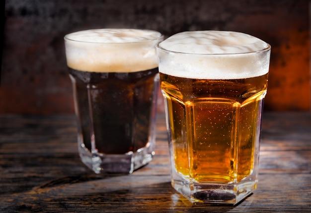 Zwei große gläser mit frisch eingegossenem dunklem und hellem bier und schaumstoffkopf auf holzschreibtisch. lebensmittel- und getränkekonzept