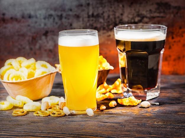 Zwei große gläser mit frisch gegossenem, hellem, ungefiltertem und dunklem bier in der nähe von tellern mit snacks und pommes auf einem dunklen holzschreibtisch. lebensmittel- und getränkekonzept