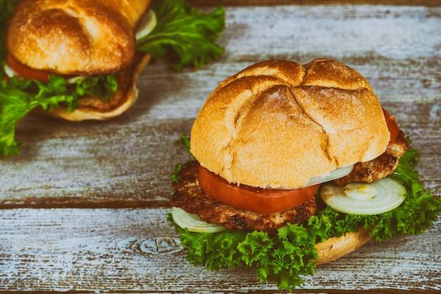 Zwei große hausgemachte leckere cheesburger mit zwiebeln, gegrilltem speck, frischen tomaten, frischem leckeren burgerholztisch