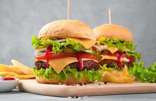 Zwei große, leckere burger und pommes frites an einer grauen wand. seitenansicht, nahaufnahme.