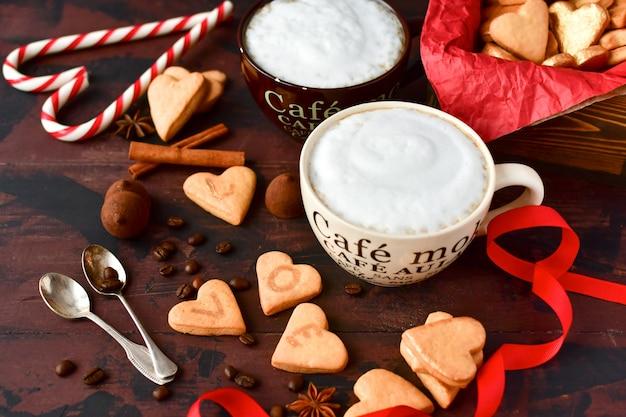 Zwei große tassen kaffee und kekse in form von herzen. romantisches frühstück, romantischer valentinstag