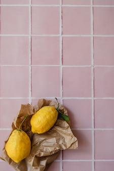 Zwei große zitronen mit einem grünen blatt in der einkaufspapiertüte auf rosafarbenem fliesenküchenarbeitsplattenhintergrund
