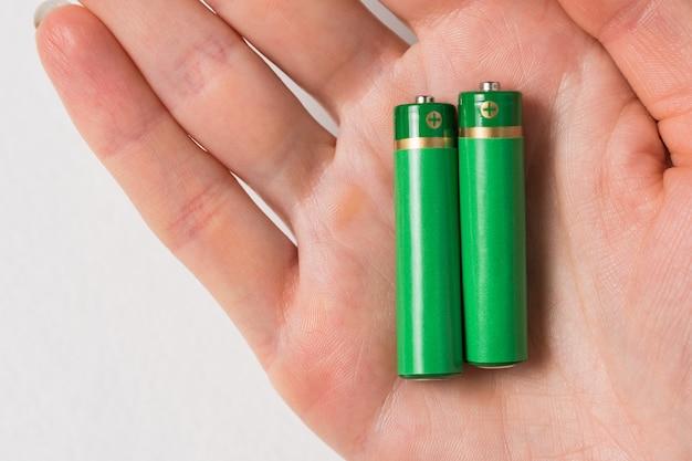 Zwei grüne aa-batterien auf der handfläche der frau. generischer akku auf weiß