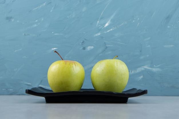 Zwei grüne äpfel auf schwarzem teller