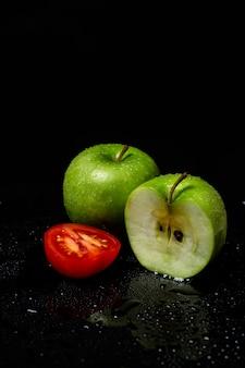 Zwei grüne äpfel und tomaten in zwei hälften geschnitten auf einem schwarzen