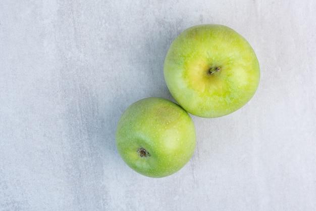Zwei grüne frische äpfel auf dem marmor.