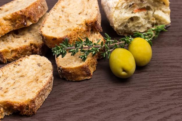 Zwei grüne oliven, thymianzweig und brotscheiben auf holztisch. nahansicht