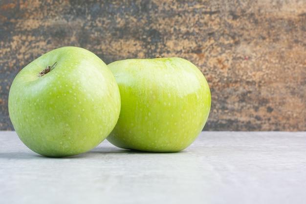 Zwei grüne reife äpfel auf dem marmor.