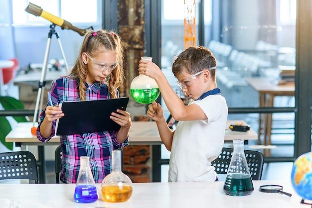 Zwei grundschüler in schutzbrille experimentieren mit farbigen flüssigkeiten in glaskolben und trockeneis.