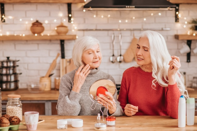 Zwei gut aussehende ältere frauen, die neue creme versuchen