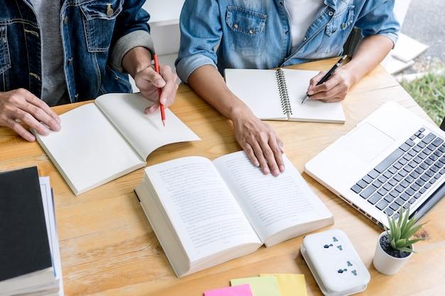 Zwei gymnasiasten oder klassenkameraden helfen freunden beim lernen von hausaufgaben im klassenzimmer