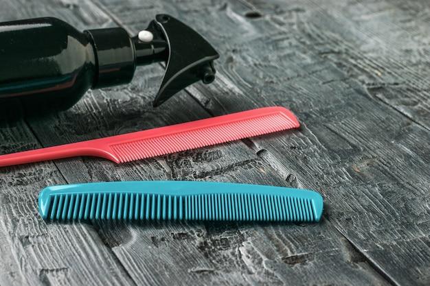 Zwei haarkämme und ein spray auf einem holztisch. ein werkzeug für die haarpflege.