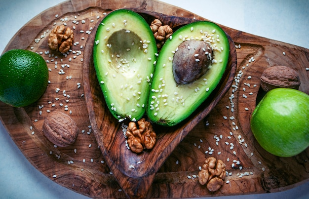 Zwei hälften avocado auf dem holzschneidebrett mit limette, apfel und walnüssen.
