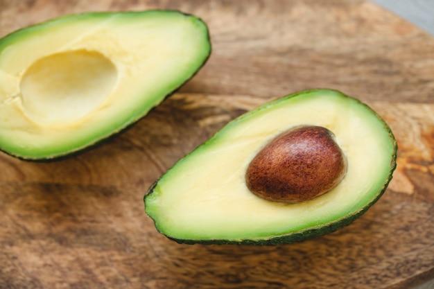 Zwei hälften der avocado auf hölzernem brett
