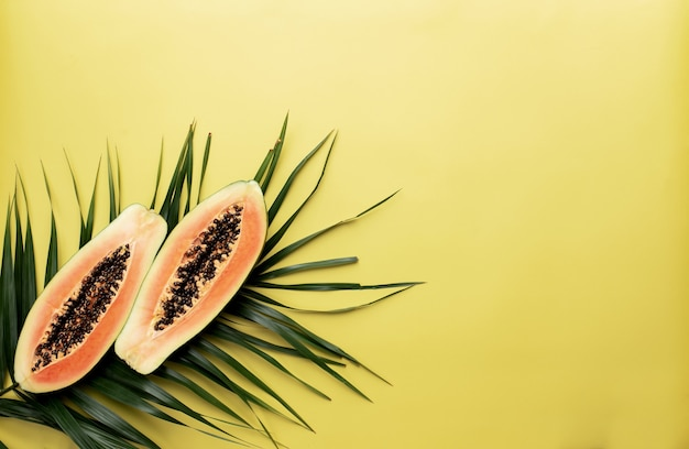 Zwei hälften der frischen tropischen papayafrucht als gesundes ernährungskonzept auf dem grünen palmblatt