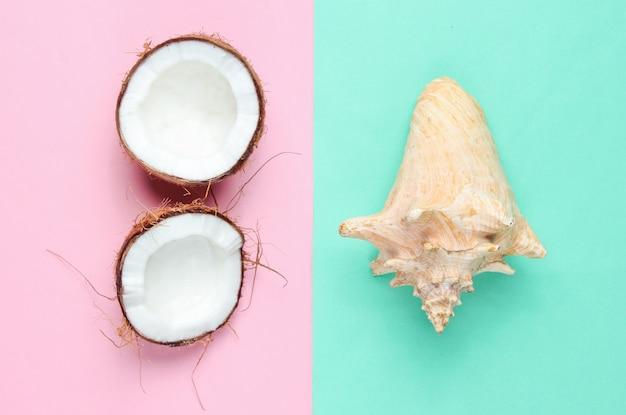 Zwei hälften der gehackten kokosnuss und der muschel auf blauem rosa pastellhintergrund