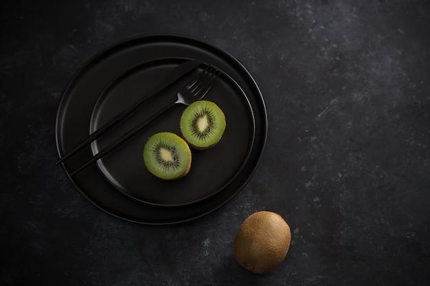 Zwei hälften der grünen kiwi auf schwarzem teller. frische reife früchte. gesundes lebensmittelkonzept.