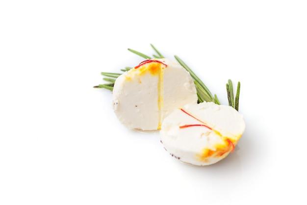 Zwei hälften der käsekugel mit thymianzweig auf weißem hintergrund
