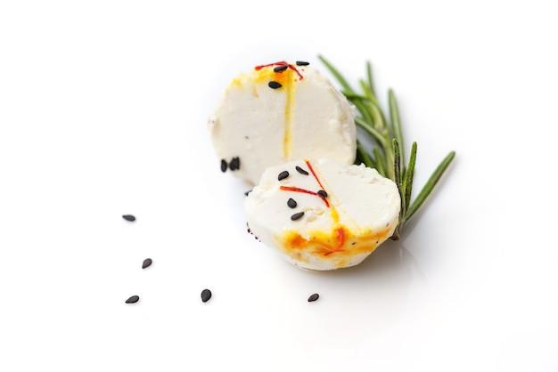 Zwei hälften der käsekugel mit zweig thymian und sesam auf weißem hintergrund
