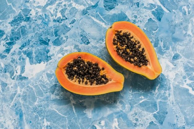 Zwei hälften der papaya auf einem hellen blauen hintergrund