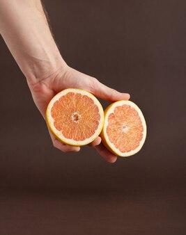 Zwei hälften einer geschnittenen grapefruit auf der hand des mannes