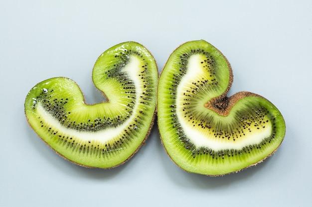 Zwei hälften einer herzförmigen hässlichen kiwi in einem abschnitt auf einer grauen oberfläche.