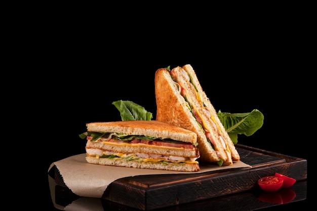 Zwei hälften eines club-sandwichs auf kraftpapier und braunem holzschneidebrett.