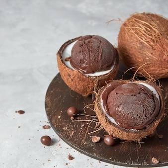 Zwei hälften kokosnuss mit hausgemachtem schokoladendessert auf einem holzbrett auf einem grauen tisch mit kopienraum.