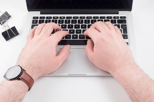 Zwei hände, die auf laptop schreiben