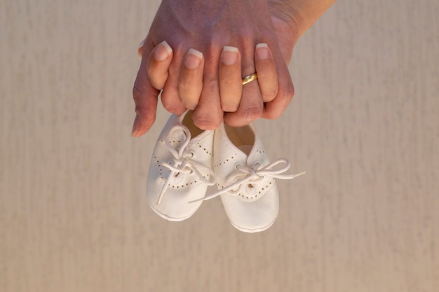 Zwei hände, die babyschuhe halten. schwangerschaftskonzept.