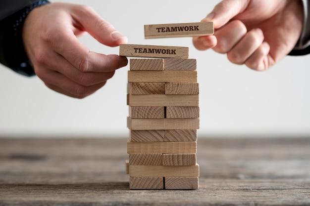 Zwei hände, die dominosteine auf stapel von holzsteinen mit geschäftszeichen der teamarbeit setzen