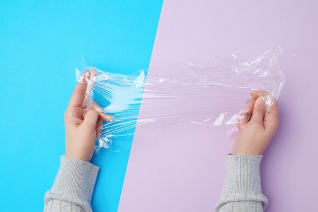 Zwei hände, die ein stück transparenten plastikfilm halten