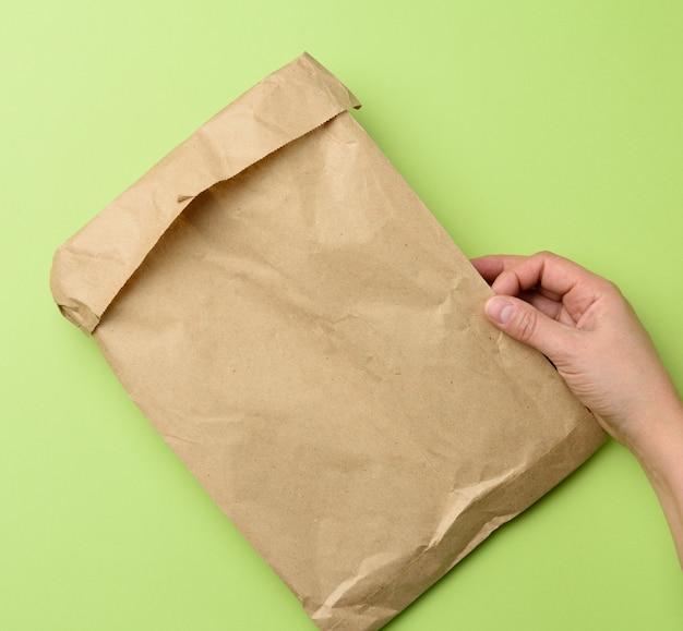 Zwei hände, die eine papiertüte des braunen kraftpapiers auf grün halten