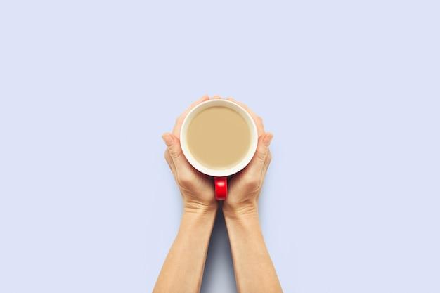 Zwei hände, die eine tasse mit heißem kaffee auf einem blauen hintergrund halten. frühstückskonzept mit kaffee oder tee. guten morgen, nacht, schlaflosigkeit. flache lage, draufsicht