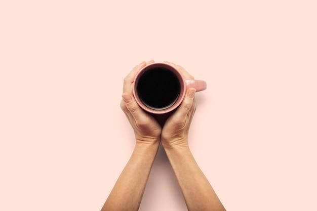 Zwei hände, die eine tasse mit heißem kaffee auf einem rosa hintergrund halten. frühstückskonzept mit kaffee oder tee. guten morgen, nacht, schlaflosigkeit. flache lage, draufsicht
