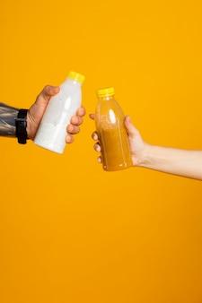 Zwei hände, die flaschen mit getränken im studio auf gelbem hintergrund halten