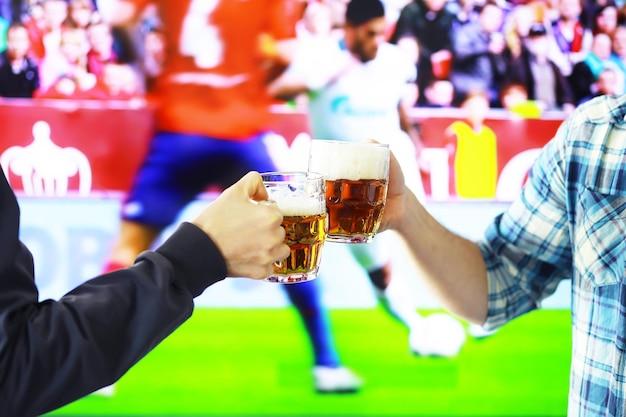 Zwei hände, die horizontales lagerbierglas halten und auf dem hintergrund des fußballspiels klirren. sportfans jubeln. freunde freizeit-lifestyle-konzept.