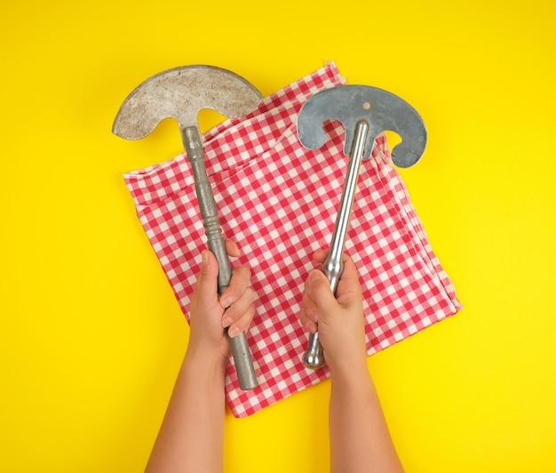 Zwei hände, die scharfe küchenmesser der weinlese für fleisch und gemüse halten