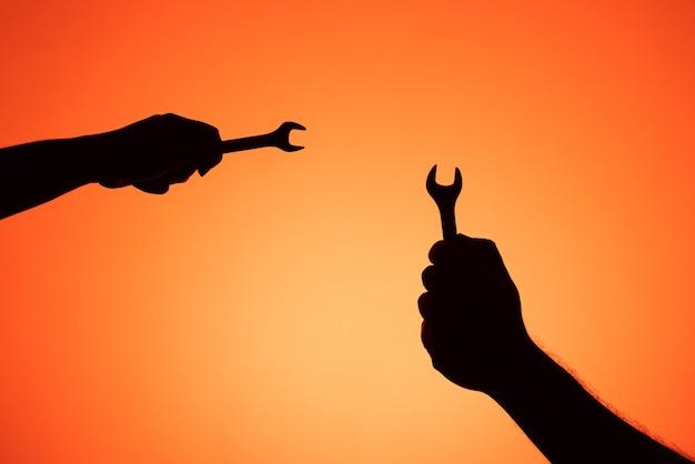 Zwei hände, die schraubenschlüssel halten. silhouettenfotos