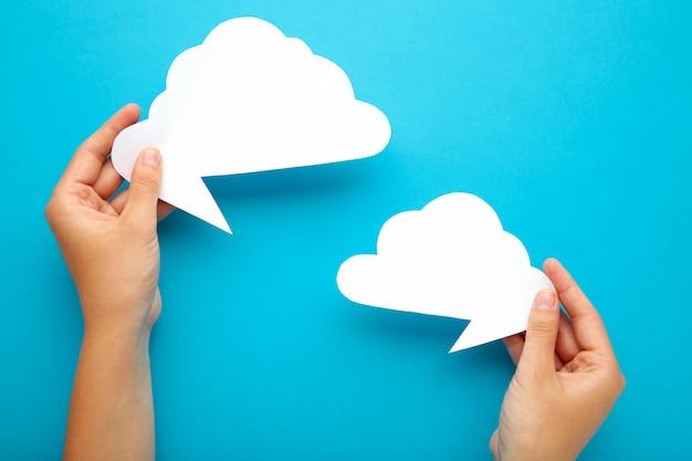 Zwei hände, die sprechblasen auf blau halten. dialog